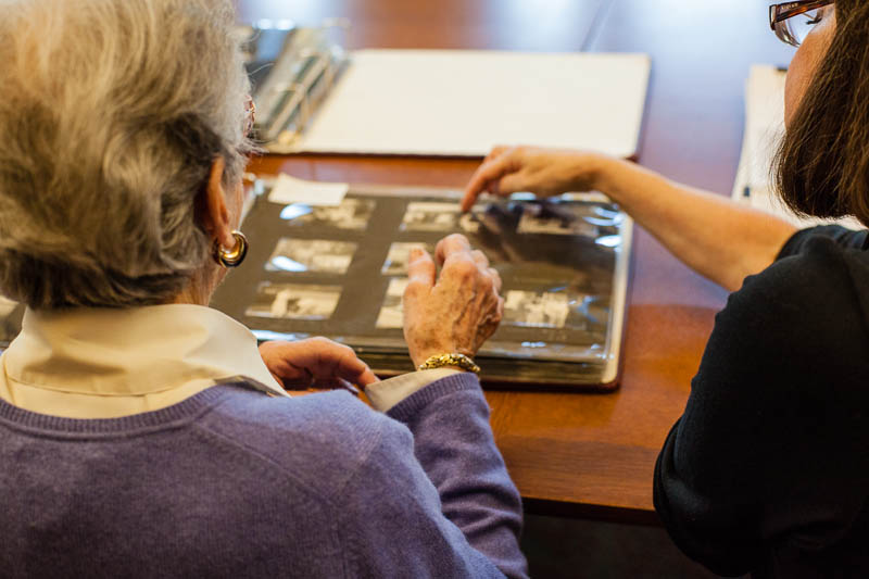 Clare Clark, Carnegie Library archivist, points out a photo from the archive to Mrs. Natalie Meyer, former employee of the lab from 1949-50
